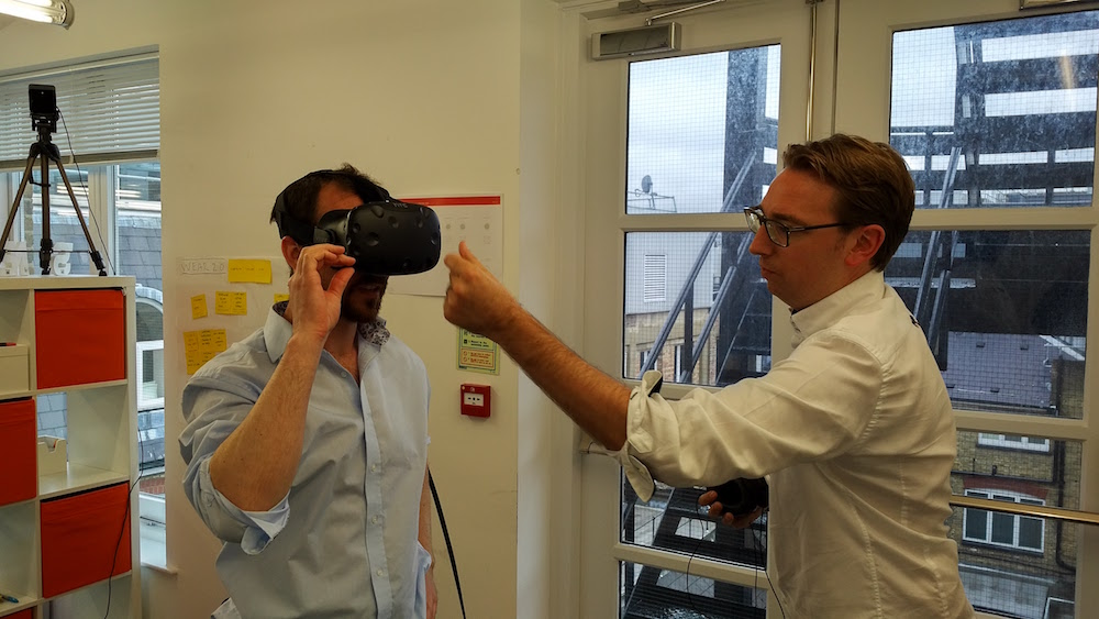 Alex (left) wearing HTC Vive with Greg setting up